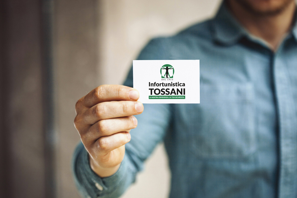 mano che regge il biglietto da visita dell'Infortunistica Tossani