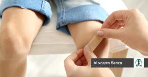 donna applica cerotto sul ginocchio di un bimbo, Infortunistica Tossani